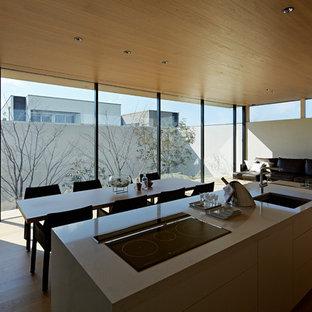 Idéer för att renovera en funkis matplats med öppen planlösning, med vita väggar, plywoodgolv och beiget golv