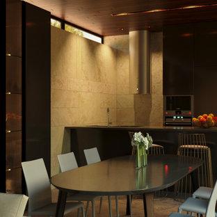 Esempio di una sala da pranzo aperta verso il soggiorno etnica con pareti beige, pavimento in travertino, stufa a legna, cornice del camino in pietra e pavimento grigio