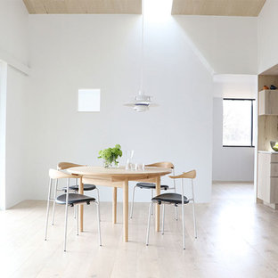Example of a danish light wood floor and white floor great room design in Other with white walls, a wood stove and a wood fireplace surround