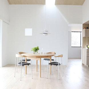 他の地域の北欧スタイルのおしゃれなLDK (白い壁、淡色無垢フローリング、薪ストーブ、木材の暖炉まわり、白い床) の写真