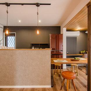 他の地域の小さいコンテンポラリースタイルのおしゃれなLDK (黒い壁、無垢フローリング、茶色い床、暖炉なし、クロスの天井、板張り壁) の写真