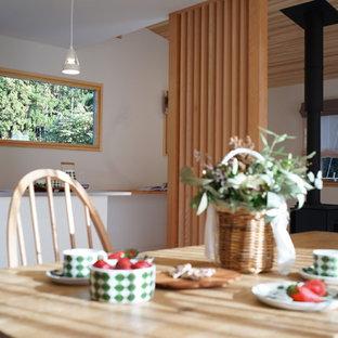 Esempio di una sala da pranzo aperta verso il soggiorno moderna con pareti bianche, parquet chiaro, stufa a legna, cornice del camino in pietra e pavimento bianco