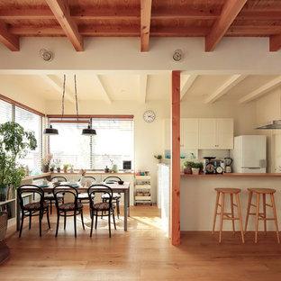 他の地域のコンテンポラリースタイルのおしゃれなLDK (白い壁、無垢フローリング、薪ストーブ、レンガの暖炉まわり、ベージュの床) の写真