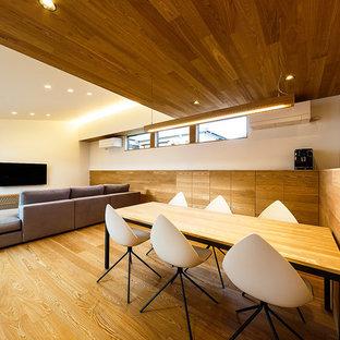 Modelo de comedor minimalista, de tamaño medio, abierto, con paredes blancas, suelo de contrachapado y suelo marrón