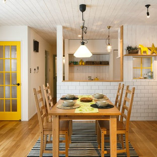 Example of a small country light wood floor kitchen/dining room combo design in Other with white walls