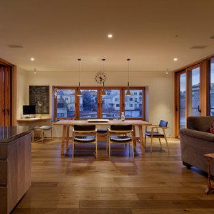 東京23区の広いアジアンスタイルのおしゃれなLDK (白い壁、無垢フローリング、標準型暖炉、タイルの暖炉まわり、茶色い床) の写真