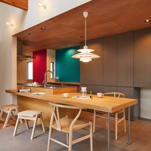 Immagine di una sala da pranzo aperta verso la cucina moderna di medie dimensioni con pareti marroni, pavimento in sughero, nessun camino e pavimento grigio