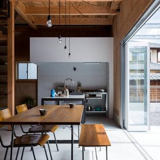 Modelo de comedor de cocina urbano, de tamaño medio, con paredes blancas, suelo de cemento y suelo gris