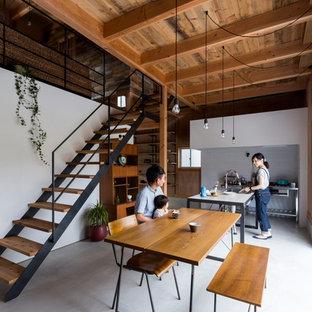 Immagine di una sala da pranzo aperta verso la cucina stile rurale di medie dimensioni con pareti multicolore, pavimento in cemento e pavimento grigio