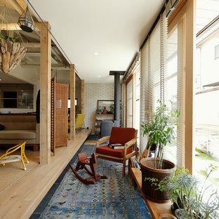 Immagine di una sala da pranzo minimalista con pareti bianche, parquet chiaro e stufa a legna