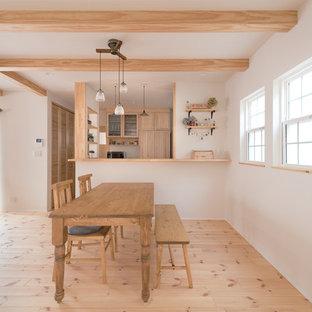 Ispirazione per una sala da pranzo aperta verso il soggiorno etnica con pareti bianche, parquet chiaro e pavimento marrone