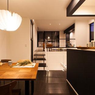 他の地域の小さいミッドセンチュリースタイルのおしゃれなダイニングキッチン (白い壁、合板フローリング、黒い床) の写真