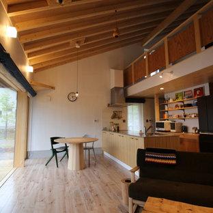 Idee per una piccola sala da pranzo aperta verso il soggiorno rustica con pareti bianche, pavimento in compensato, stufa a legna, cornice del camino in perlinato, travi a vista e pareti in perlinato