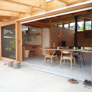 Ispirazione per una piccola sala da pranzo aperta verso il soggiorno etnica con pavimento in cemento, stufa a legna e cornice del camino in legno