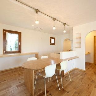 他の地域の地中海スタイルのおしゃれなLDK (白い壁、淡色無垢フローリング、暖炉なし、茶色い床) の写真