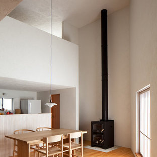 東京23区の北欧スタイルのおしゃれなダイニング (白い壁、無垢フローリング、薪ストーブ、石材の暖炉まわり、茶色い床) の写真