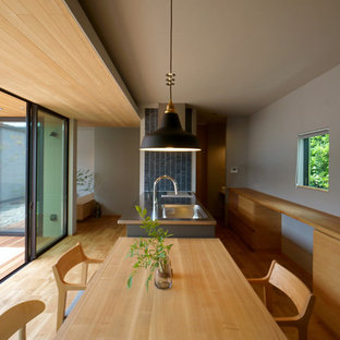 他の地域のコンテンポラリースタイルのおしゃれなLDK (グレーの壁、無垢フローリング、茶色い床) の写真