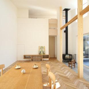 他の地域のモダンスタイルのおしゃれなダイニング (白い壁、淡色無垢フローリング、薪ストーブ、コンクリートの暖炉まわり、ベージュの床) の写真