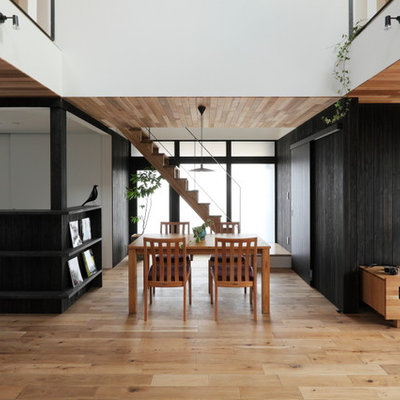 Example of a mid-sized medium tone wood floor and beige floor dining room design in Other with black walls