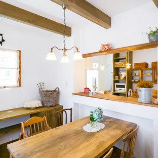Imagen de comedor mediterráneo, pequeño, abierto, con paredes blancas, suelo de madera oscura y suelo marrón