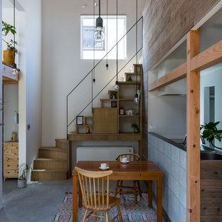 Foto di una sala da pranzo aperta verso la cucina etnica di medie dimensioni con pareti bianche, pavimento in cemento e pavimento grigio