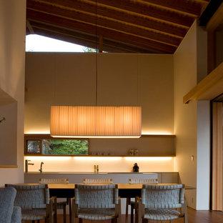 Immagine di una sala da pranzo etnica con pareti bianche, pavimento in legno massello medio e pavimento marrone