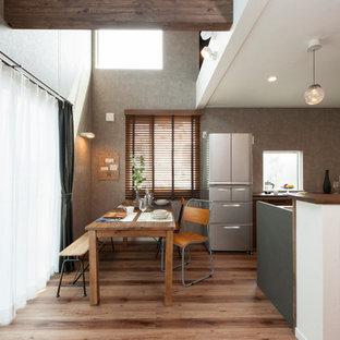 他の地域の中くらいのインダストリアルスタイルのおしゃれなダイニング (グレーの壁、暖炉なし、茶色い床) の写真