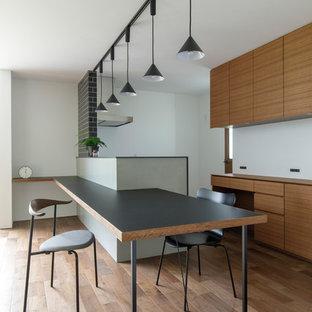 Ejemplo de comedor de cocina asiático con paredes grises, suelo de madera en tonos medios y suelo marrón