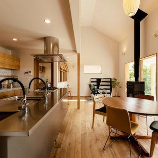 他の地域のアジアンスタイルのおしゃれなLDK (白い壁、淡色無垢フローリング、薪ストーブ、茶色い床) の写真