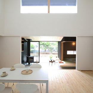 Aménagement d'une salle à manger ouverte sur le salon moderne de taille moyenne avec une cheminée d'angle, un mur blanc, un sol en bois clair, un manteau de cheminée en béton et un sol beige.