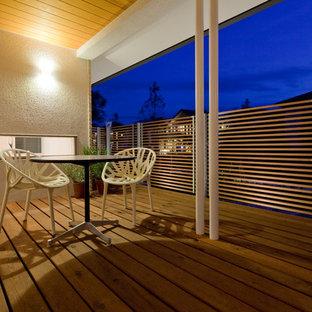 Immagine di un grande patio o portico etnico davanti casa con pedane e un tetto a sbalzo