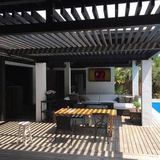 他の地域のトロピカルスタイルのおしゃれな中庭のテラス (アウトドアキッチン、デッキ材舗装、パーゴラ) の写真