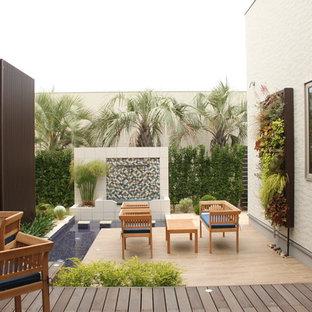 他の地域のトロピカルスタイルのおしゃれな中庭のテラス (アウトドアキッチン、デッキ材舗装、日よけなし) の写真