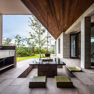 Immagine di un patio o portico etnico di medie dimensioni e davanti casa con un focolare, piastrelle e un tetto a sbalzo