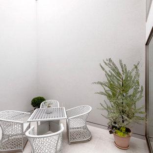 モダンスタイルのおしゃれな中庭のテラス (タイル敷き) の写真