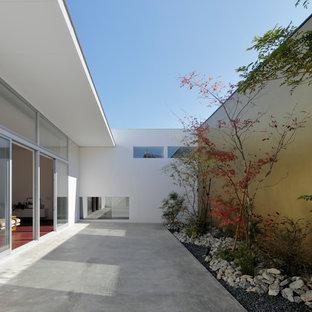 他の地域のモダンスタイルのおしゃれなテラス・中庭 (コンクリート敷き、張り出し屋根) の写真