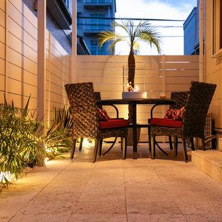 Idee per un patio o portico costiero nel cortile laterale con pavimentazioni in pietra naturale e un parasole