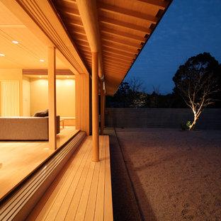 Immagine di un piccolo patio o portico etnico davanti casa con pedane e un tetto a sbalzo