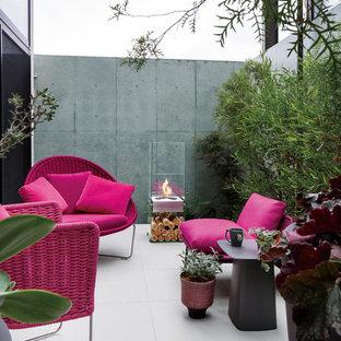 Esempio di un patio o portico bohémian in cortile con un focolare e un tetto a sbalzo