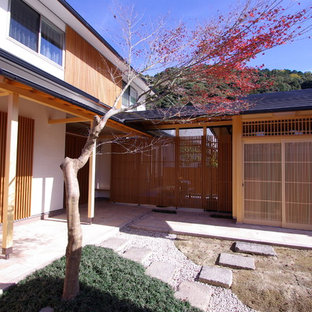World-inspired front patio in Kyoto with decomposed granite and a roof extension.