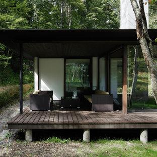Idee per un patio o portico moderno davanti casa con pedane e un tetto a sbalzo