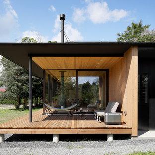Idee per un patio o portico etnico davanti casa con pedane e un tetto a sbalzo