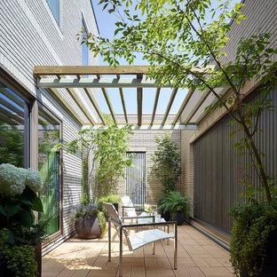 Esempio di un patio o portico etnico di medie dimensioni con un parasole