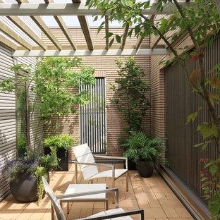 Esempio di un patio o portico etnico con un parasole