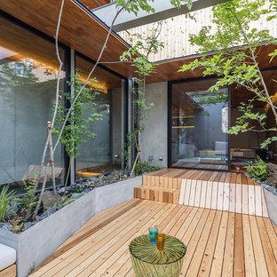 他の地域のコンテンポラリースタイルのおしゃれな中庭のテラス (デッキ材舗装、張り出し屋根) の写真