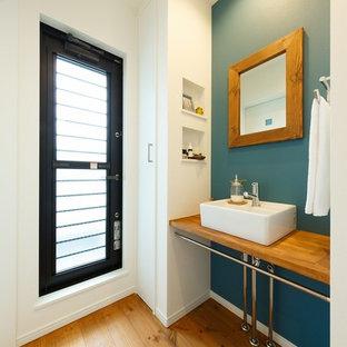 На фото: туалет в скандинавском стиле с синими стенами, паркетным полом среднего тона, настольной раковиной, столешницей из дерева, оранжевым полом и коричневой столешницей с