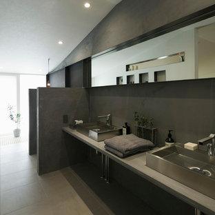 他の地域の小さいエクレクティックスタイルのおしゃれなトイレ・洗面所 (グレーの壁、ベッセル式洗面器、コンクリートの洗面台、グレーの床、オープンシェルフ、グレーのタイル、グレーの洗面カウンター) の写真