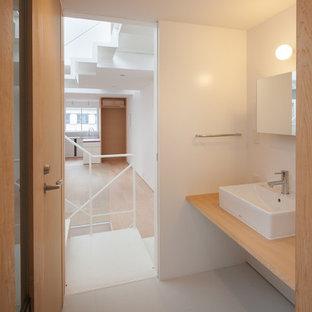 Пример оригинального дизайна: туалет среднего размера в стиле модернизм с унитазом-моноблоком, белой плиткой, белыми стенами, полом из линолеума, настольной раковиной и столешницей из дерева