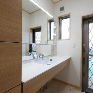 Imagen de aseo de estilo zen, grande, con armarios tipo mueble, puertas de armario de madera clara, paredes blancas, suelo laminado, lavabo integrado, encimera de acrílico, suelo beige y encimeras blancas