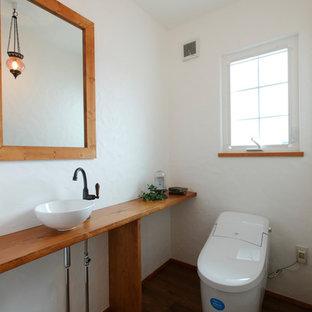 他の地域の地中海スタイルのおしゃれなトイレ・洗面所 (オープンシェルフ、白い壁、濃色無垢フローリング、ベッセル式洗面器、木製洗面台、茶色い床、ブラウンの洗面カウンター) の写真